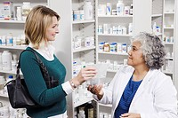 Pharmacist giving prescription to customer