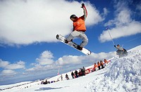 A snowboarder performs a jump in a competition. Serra da Estrela, Portugal