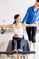 Personal trainer guiding Native American woman on pilates equipment