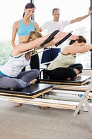Native American personal trainer smiling at woman on pilates equipment