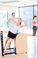 Instructor guiding woman on pilates equipment