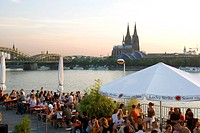 People at trendy Rheinterrassen bar and restaurant beside the River Rhine, with the old town and cathedral beyond, Cologne, North Rhine Westphalia, Ge...