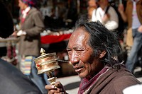 Tibetan man with prayer wheel in his hand Jokhang Kora Lhasa Tibet China