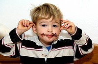 Boy with chocolate in his face