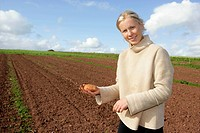 farm worker holds potato