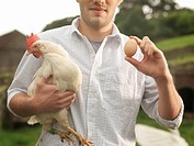 Farmer Holding Egg And Hen