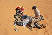 Ambulance officer is helps a injured person in desert