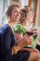 Two Caucasian women sitting with red wine glasses on sofa in living room, side view