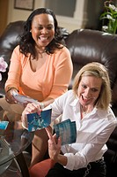 Two happy multi_ethnic women showing photographs in living room