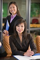 Portrait of two young Asian businesswomen sitting in conference room with files