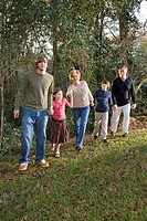 Portrait of family holding hands along edge of forest