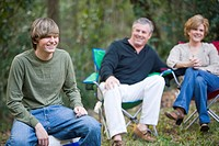 Family sitting outdoors together, parents and teenage son