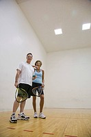 Portrait of mature couple playing in an indoor racquetball court