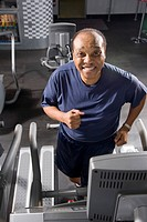 Senior man walking on treadmill at health gym, looking at camera