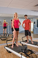 Portrait of young man and young woman standing on Pilates exercise equipment in gym with mirror in background
