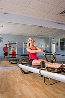 Young woman sitting on Pilates exercise equipment in gym while young man standing with mirror in background