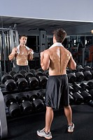 Young man standing by dumbbells in gym looking in mirror