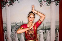 Portrait of Indian woman dancing in traditional dress in front of mural, looking at camera