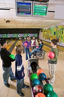 Multi_ethnic teenagers holding bowling balls and girl in wheelchair at bowling alley
