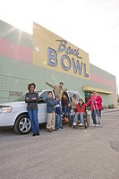Portrait of multi_ethnic teenagers and woman with crutches standing next to mini van in bowling alley parking lot