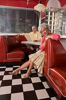 Portrait of senior couple sitting in booth of old_fashioned diner, looking at camera