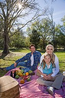 Portrait of young happy family in park with picnic basket