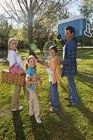 Portrait of young happy family carrying picnic basket and cooler in park