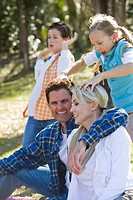 Young happy family in park, girl putting hand on parent´s head