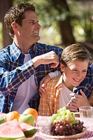 Father and son sitting at picnic table near campsite