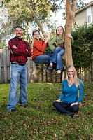 Portrait of happy young family beside tree in backyard, looking at camera