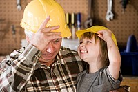 Happy grandfather and grandson wearing hard hats in garage