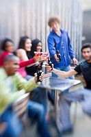Happy multi_ethnic young adults toasting their drinks outside at patio party, blurred effect
