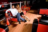Young African American couple sitting on leather couch at nightclub, high angle view