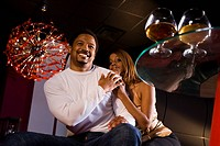 Young African American couple sitting at nightclub, brandy glasses on table, low angle view