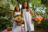 Portrait of happy elementary age African American girls holding flower baskets near picnic blanket in backyard