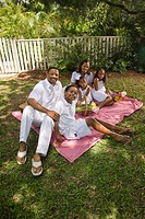 Portrait of happy African American family posing on picnic blanket in yard