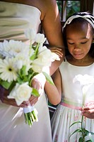 Close_up of bride with serious flower girl on her arm
