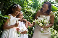 Happy African American bride holding bouquet outside with flower girls on wedding day