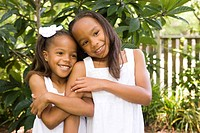Happy African American girls hugging affectionately outdoors