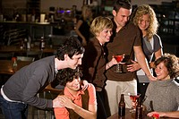 Young friends hanging out and drinking at bar together and enjoying themselves