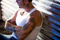 Mid adult man with tattoo design on arms