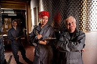 Winery workers standing next to wine vats