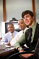 Three multiculltural businessmen in conference room looking in same direction