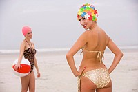 Two young women in retro swim caps and swimsuits with beach ball on beach