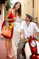 Attractive young woman standing on side walk, talking to handsome young man on motor scooter