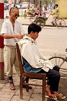 A street hair stylist on the pavement in the centre of the city of Hanoi, Vietnam, Indochina, Southeast Asia, Asia