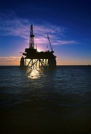 Silhouette of oil platform against moody sky at sunset