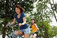 woman and young girl riding tandem bike