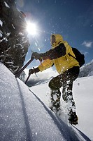 Mountaineer climbing snow covered mountain