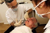 Watched by his assistant, a dentist injects a local pain killing anaesthetic into a patient´s gum to numb the surrounding area before starting a denta...